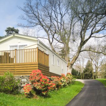 A Caravan Holiday Home surrounded by flowers at Skelwith Fold Caravan Park
