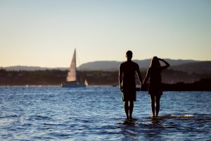 Couple watching a boat pass by during their romantic Lake District getaway